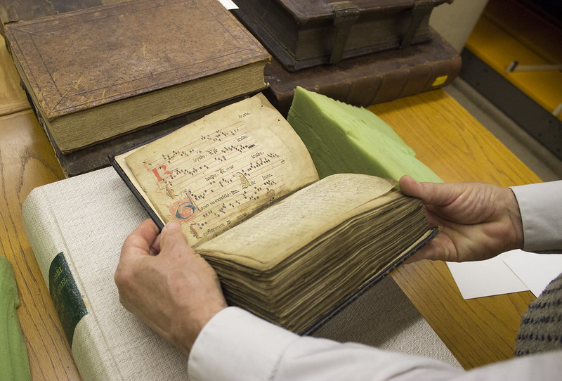 """Librarian of Saint Meinrad Theological Seminary showcasing one of the many books in the library's """"Rare Book Room"""""""